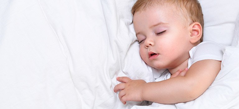 baby napping on bed